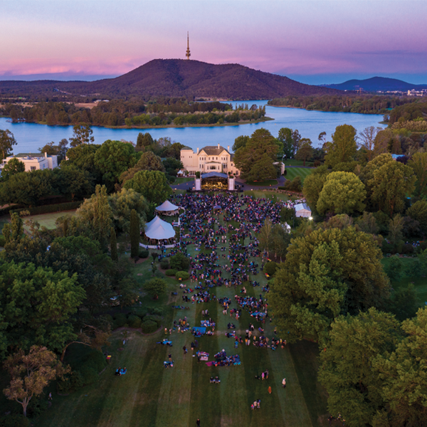 Aerial image of outdoor concert on the lawns of Government House. People are sitting in groups on the lawn in front of the stage, with Government House in the background and a sunset over Lake Burley Griffin.